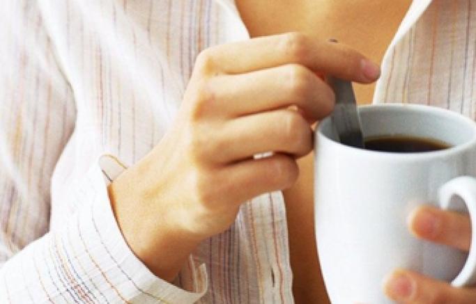 Kvinne rører i kaffekopp
