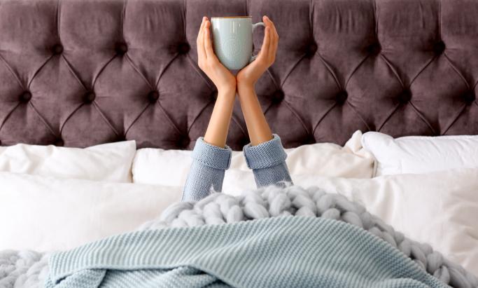 Kvinne drikker kaffe i sengen