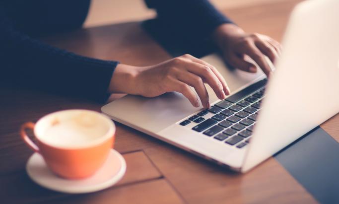 En kopp kaffe og en kvinne som jobber ved en MacBook
