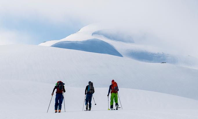 Tre skigåere i snødekt fjell