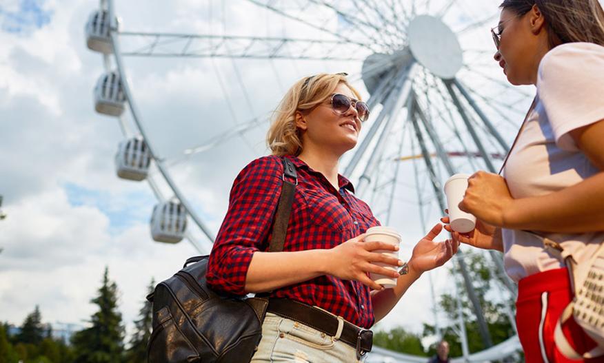 To kvinner drikker kaffe foran pariserhjul