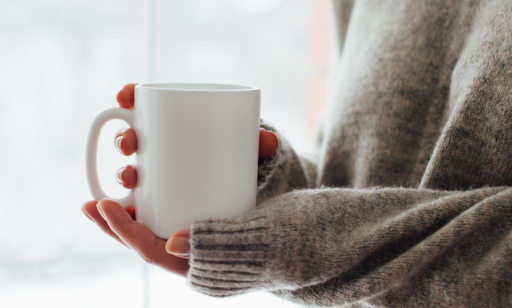 Hender varmer seg på et krus med kaffe