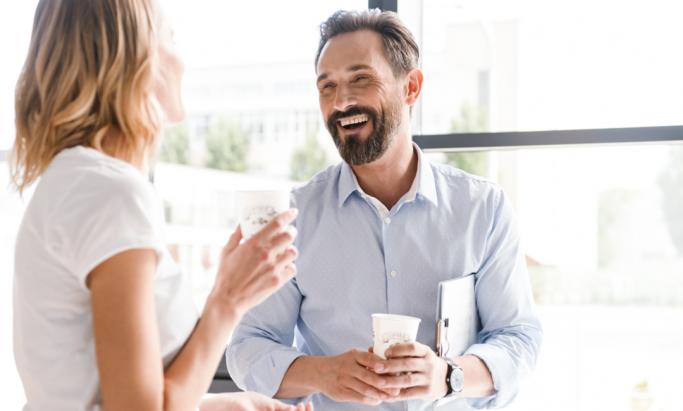 En kvinne og en mann drikker kaffe og smiler