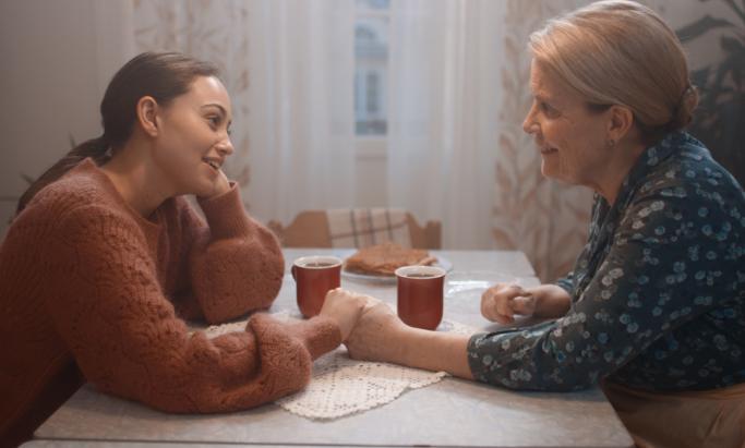bestemor og barnebarn ved kjøkkenbord over en kopp kaffe