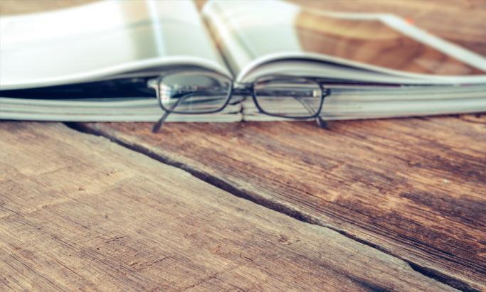 produktkatalog og briller på et bord